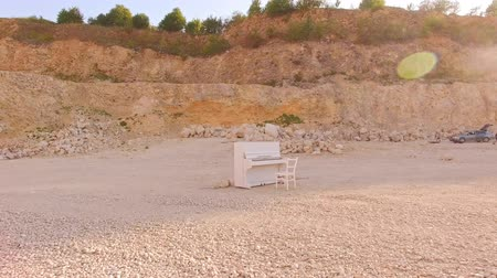 zongora : white piano and a white chair stand on a yellow sand against the background of the rocks. Interesting story. Aerial view
