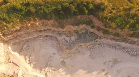 mirage : quadrocopter is flying over a deep yellow ravine. The pianist is playing on a white piano on yellow sand. Aerial view from the birds eye view. Stunning story.