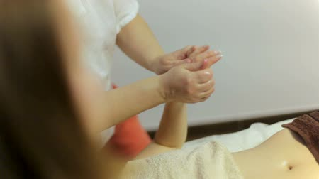 revitalizing : Two masseuses massage the hands of a girl in a spa salon. Ayurvedic massage in four hands