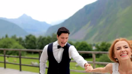 mediaeval : Wedding day. Happy newlyweds have fun against the backdrop of the mountains. Stock Footage