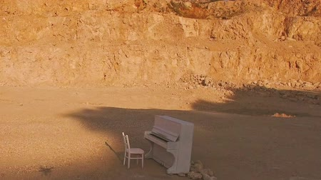 mirage : white piano and a white chair stand on a yellow sand against the background of the rocks. Interesting story. Aerial view