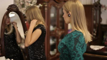 naszyjnik : Two beautiful girls choose jewelry in front of a mirror in a chic room