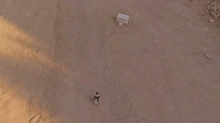 enchanted princess : enchanted girl walks through the desert to the white piano. A strange dream. Aerial view.
