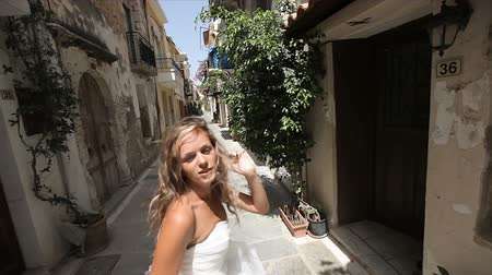 восхитительный : wedding day. Merry happy young woman runs along the street of the old city and looks back. Slow motion