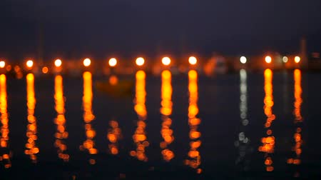 varoşlarda : Bright lights are reflected in the dark sea water at the pier with boats. bokeh. Stok Video