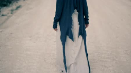 unrequited : sad young woman in ethnic clothes walks along the white road. Unrequited love.