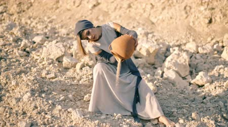 rito : girl in ethnic dress sits near the road and pours sand out of the pitcher. The water turned into sand Vídeos