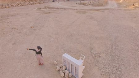 surrealismo : Surrealistic plot. A girl and a white piano on the background of a sand pit and a lorry Aerial view. Stock Footage