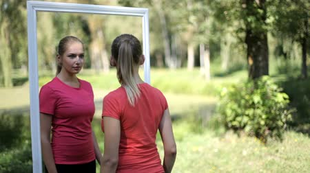 learning to walk : Two twin girls in sports clothes in the park as a reflection in the mirror
