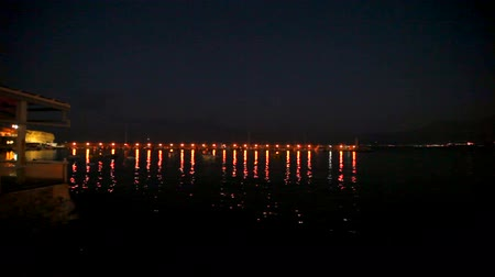 галоген : Bright lights are reflected in the dark sea water at the pier with boats. bokeh. Стоковые видеозаписи