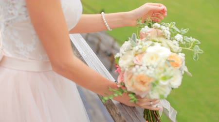 fiancee : Beautiful bride with a bouquet of flowers on a background of a fruit garden Stock Footage