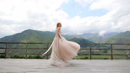 fiancee : A beautiful bride is having fun and whirls in the background of the mountains