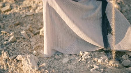 louça de barro : girl in ethnic dress sits near the road and pours sand out of the pitcher. The water turned into sand Stock Footage