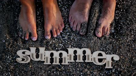 toes : Romantic guy and girl are standing on the wet sand of the beach near the word summer Stock Footage