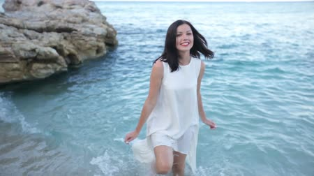 escarlate : Beautiful sexy young brunette woman in a white wet dress on the seashore in a clear sunny summer day
