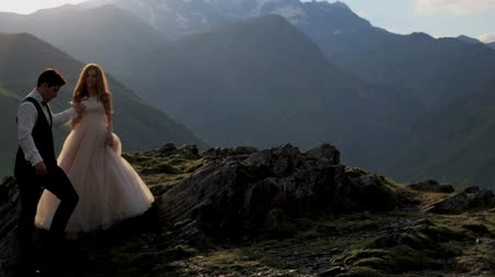 unutulmayan : A magnificent bride and groom against the background of the majestic mountains in the summer at sunset. Georgia. The concept of a happy family life