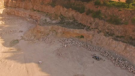 mirage : man plays the piano in a deep ravine. The film crew stands near the car. Air shooting of a music video in a sandy quarry Stock Footage