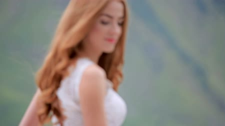 fiancee : Redhead mysterious romantic bride in a chic dress with a bouquet and the green mountains.
