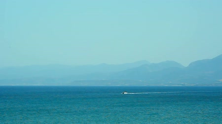 crete : motor boat in the blue sea against the background of the mountains in the morning fog