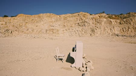 geodesy : white piano and a white chair stand on a yellow sand against the background of the rocks at sunset. surreal plot. Aerial view Stock Footage