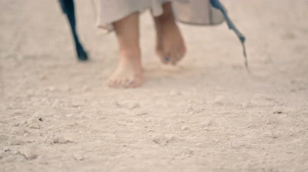 unrequited : woman in a long dress walks barefoot along the sandy road. Part of the body
