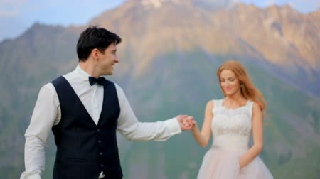 chique : Loving newlyweds walking in a meadow against the backdrop of beautiful mountains