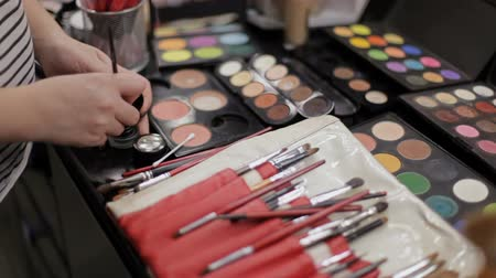 változatos : work of the make-up artist. Professional cosmetics in the make-up salon. Luxurious cosmetics for make-up. Multicolored lipstick, shadows, powder, pencils close-up