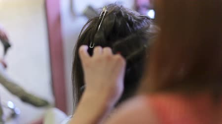ringlet : The dark-haired young woman twisting her hair into curls in hairdressers close up. Stock Footage