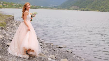 fiancee : Beautiful bride against the background of mountains and river. Wedding day Stock Footage