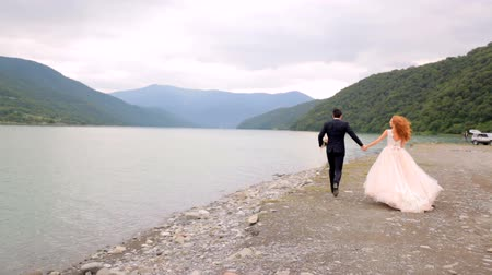 tampado : Happy bride and groom on the wedding day run along the river bank in the background of beautiful mountains. Georgia. Vídeos