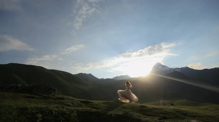 eufória : happy bride is happily spinning at sunset against the backdrop of the mountains Stock mozgókép