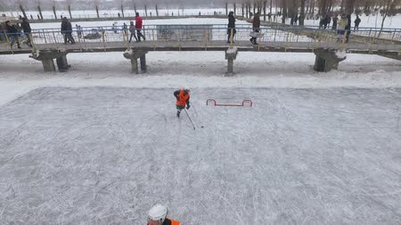 sporty zimowe : aerial view. men playing hockey on a frozen lake in a city park. Winter family fun. Ice hockey. Wideo