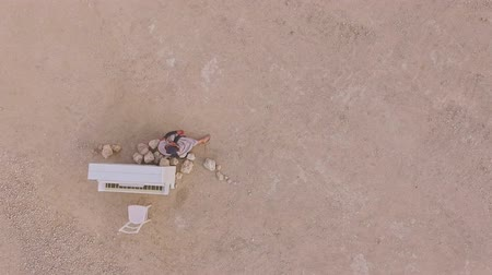 enchanted princess : Young barefoot woman sitting in the desert near a white piano. View from above. Surreal storyline. Aerial view.