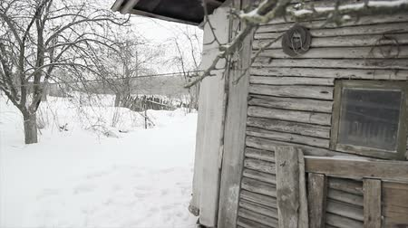 dacha : An old dilapidated wooden house with a rickety fence and an orchard near the winter.