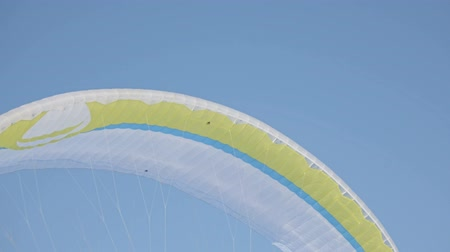 szybowiec : Winter sports . Bright yellow parachute against a blue sky
