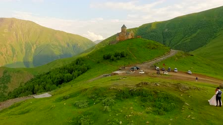 fiancee : Enamored newlyweds in the meadow against the backdrop of an old castle . Georgia. Kazbegi.
