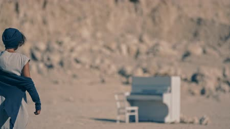 unrequited : Tired young woman walks barefoot on gravel on the background of mountains and white piano