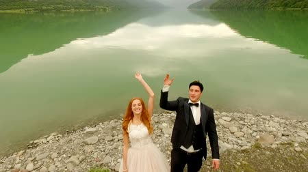tampado : Beautiful and happy bride and groom on the river bank throws a wedding bouquet in water
