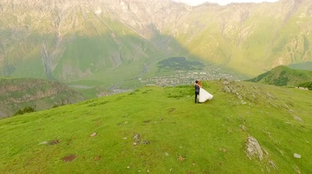 fiancee : Happy bride and groom in the background of mountains. Aerial view Slow motion