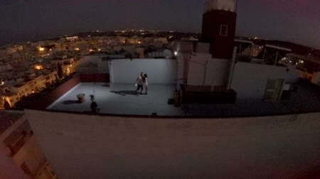 körút : Surrealism. Aerial view. The guy and the girl on the roof of a high house at night in a big city. Malta Stock mozgókép