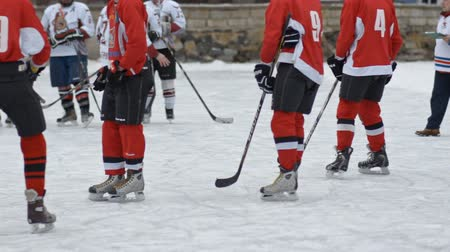 вратарь : Men play hockey on the hockey field . body parts