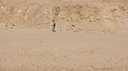 yalınayak : young woman walks barefoot through the desert amid a huge mountain.