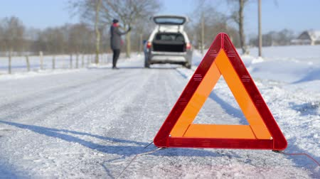 mudança : Winter Driving - Car Trouble - Woman calling roadside assistance using her cellphone.