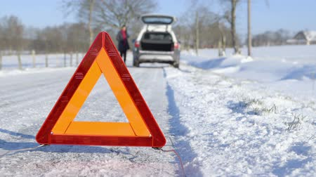 pneus : Winter Driving - Car Trouble - Car trouble on a snowy country road. Woman calling roadside assistance using her cell phone. Stock Footage