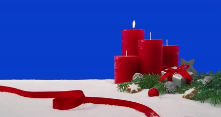 gelişi : First Sunday of Advent - four candles on a snowy table in front of a blue screen. One candle is lit, which is burning with a beautiful flame.