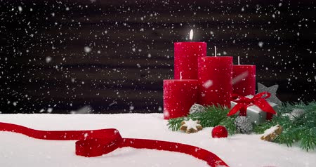gelişi : First Sunday of Advent - Beautiful snowfall in the front of a Christmas decoration on a snowy table in front of a wooden background - ProRes Stok Video