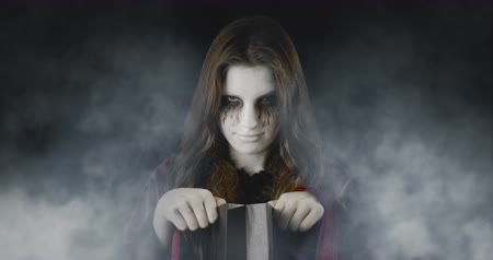 Checking the treats - teenage girl, disguised for Halloween, standing in an eerie, foggy environment - ProRes
