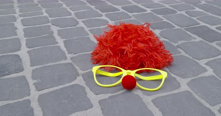 disguise : A funny wig, disguise glasses and a nose of foam on a paved ground - carnival concept or celebration concept - ProRes