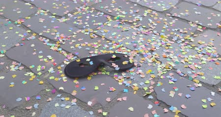 setts : A carnival mask on a street and a shower of confetti - carnival concept or celebration concept - camera pan - ProRes