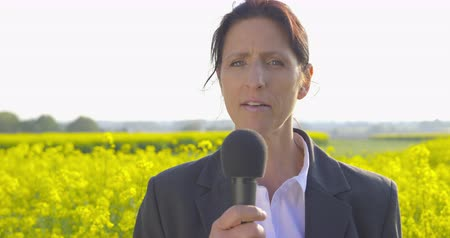 Female television reporter standing in a field of blooming rapeseed and speaking in a microphone - ProRes